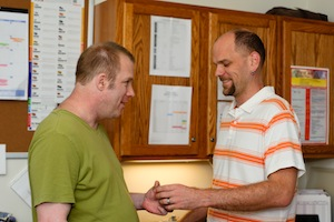 LEFT TO RIGHT: Damiano resident Patrick receiving his medication from caregiver, Xander.