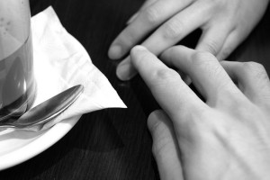 Two people hold hands on a table.